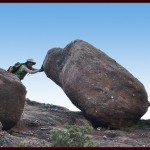 man pushing rock