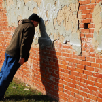 man-with-head-against-wall